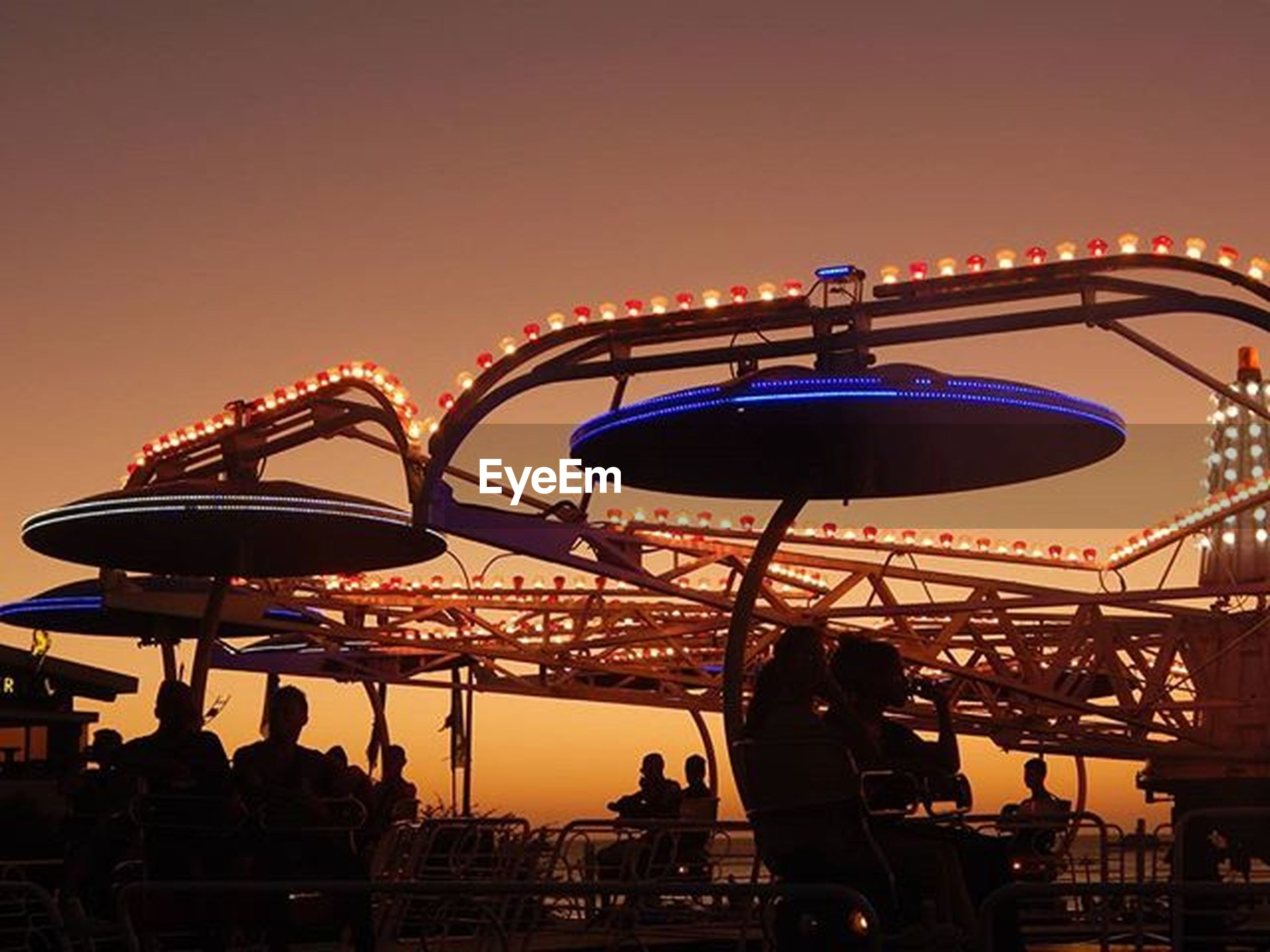 amusement park, amusement park ride, arts culture and entertainment, ferris wheel, illuminated, sky, low angle view, built structure, silhouette, architecture, clear sky, sunset, dusk, lighting equipment, copy space, leisure activity, tourism, travel destinations, large group of people, night