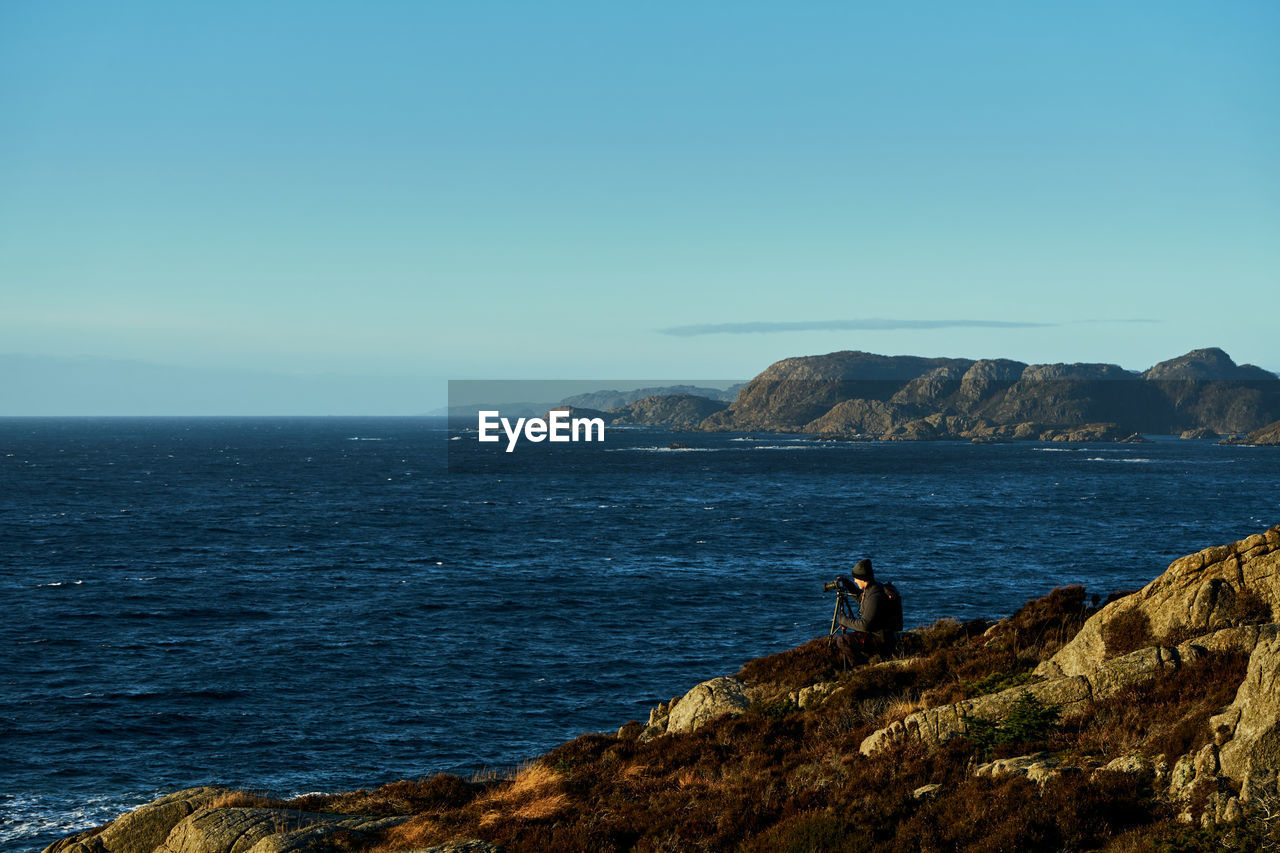 VIEW OF ROCKS ON SEA AGAINST CLEAR SKY