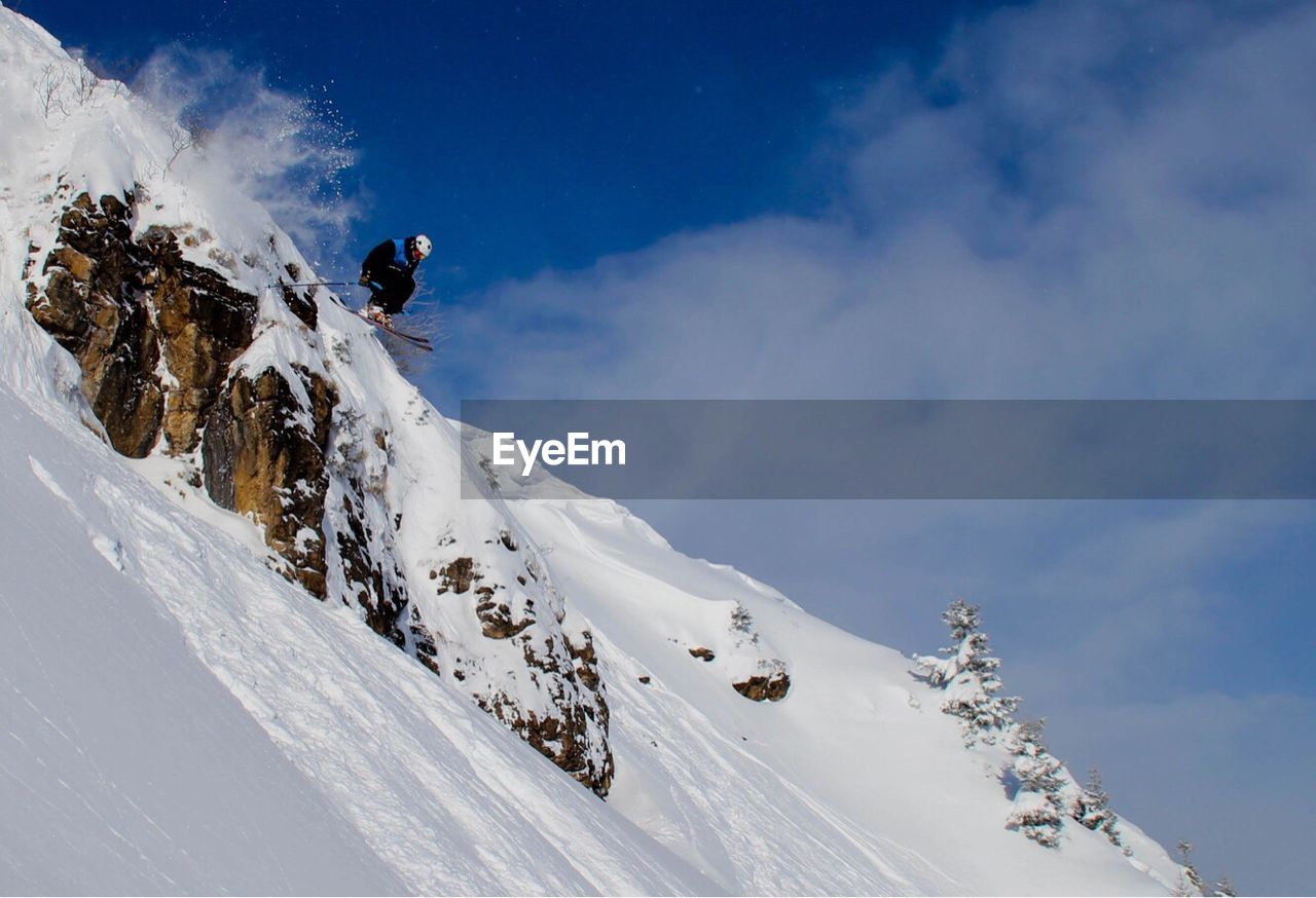 Low Angle View Of Person Skiing On Snowcapped Mountain Against Sky