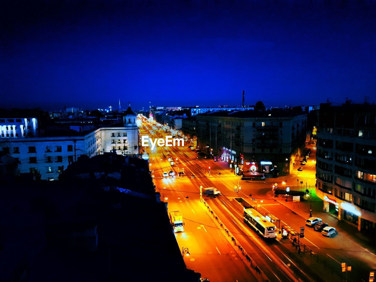 illuminated, night, city, light trail, long exposure, speed, building exterior, street, traffic, motion, road, architecture, city life, blurred motion, transportation, outdoors, high angle view, no people, built structure, cityscape, blue, high street, clear sky, sky