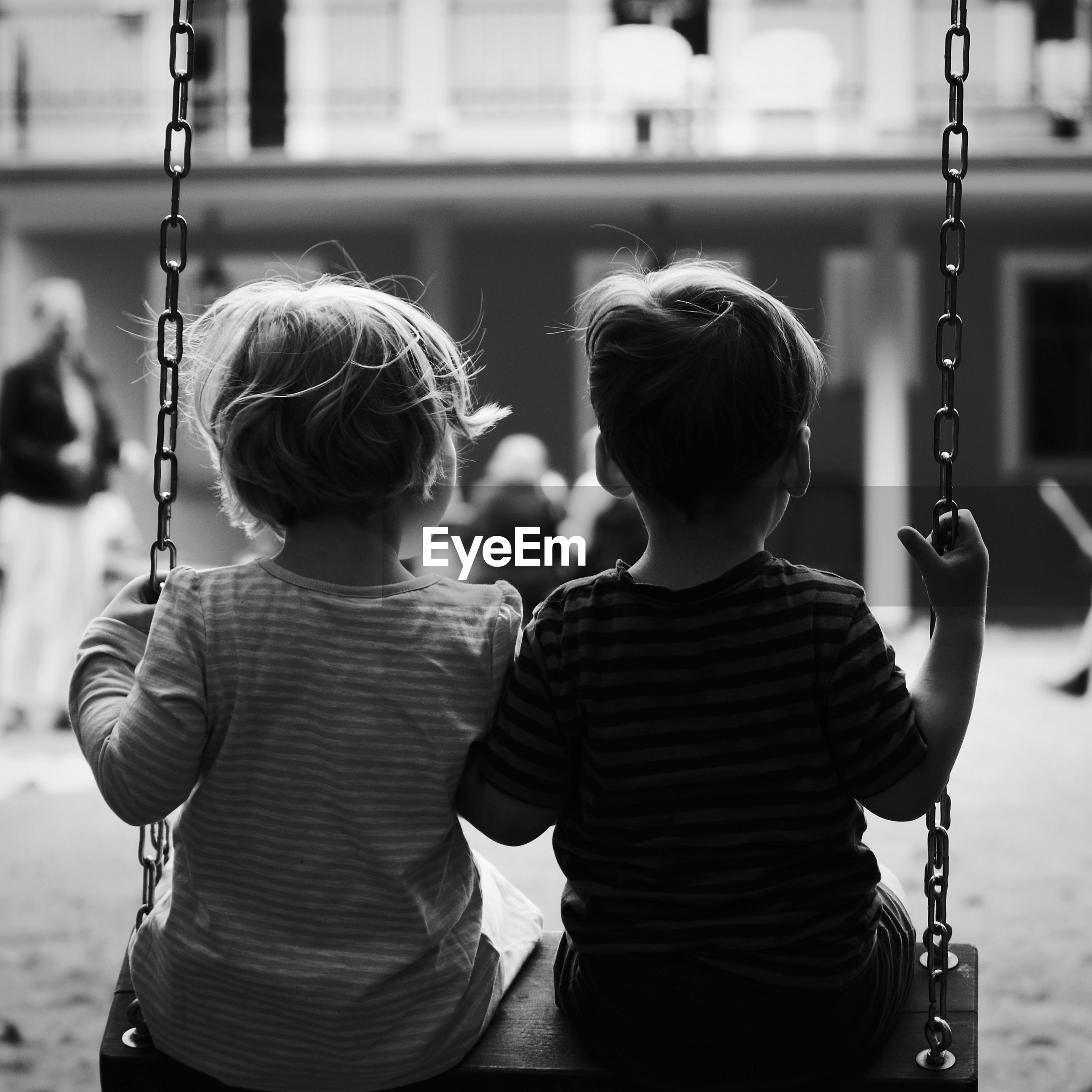 Rear view of siblings sitting on swing at playground