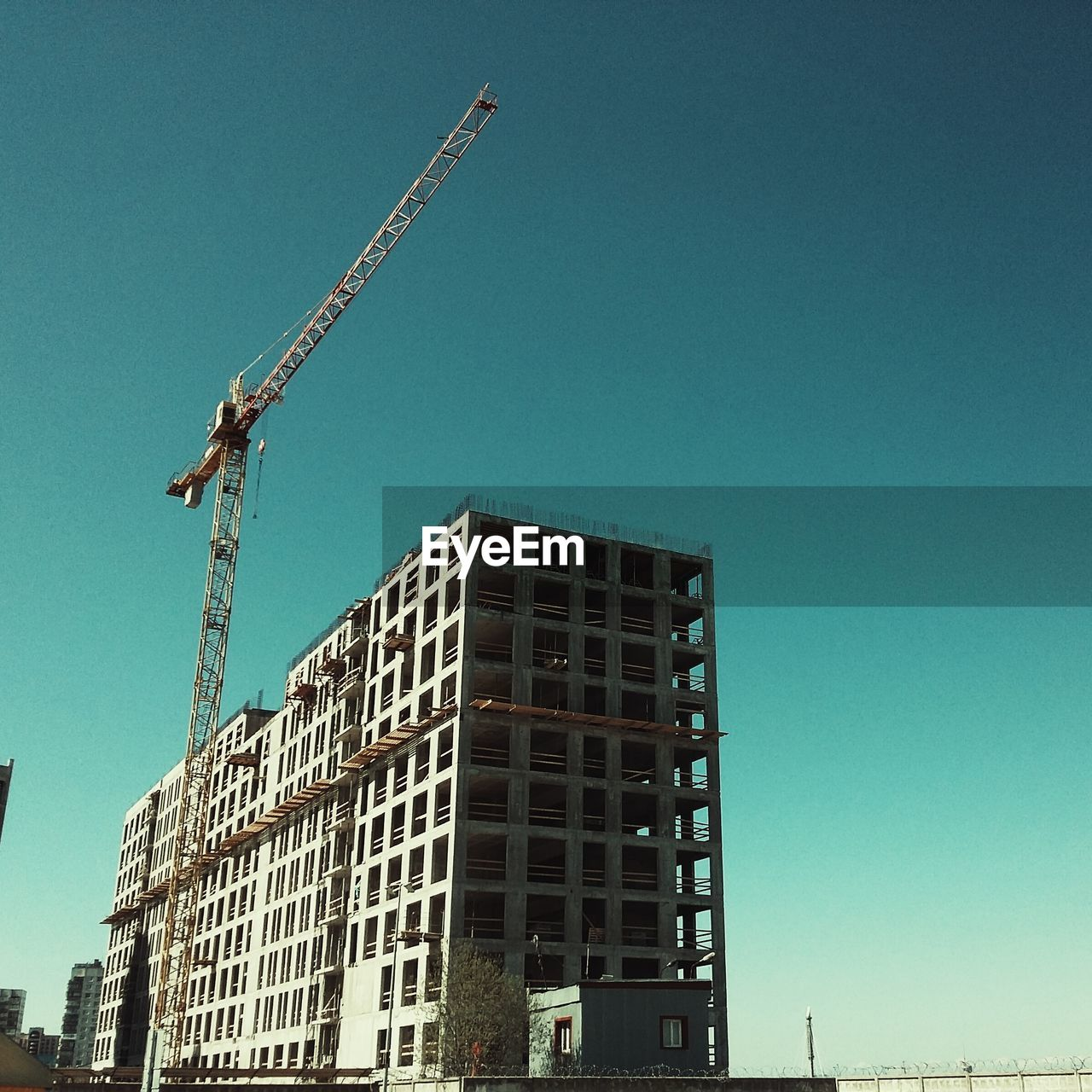Low Angle View Of Crane By Incomplete Buildings Against Clear Sky