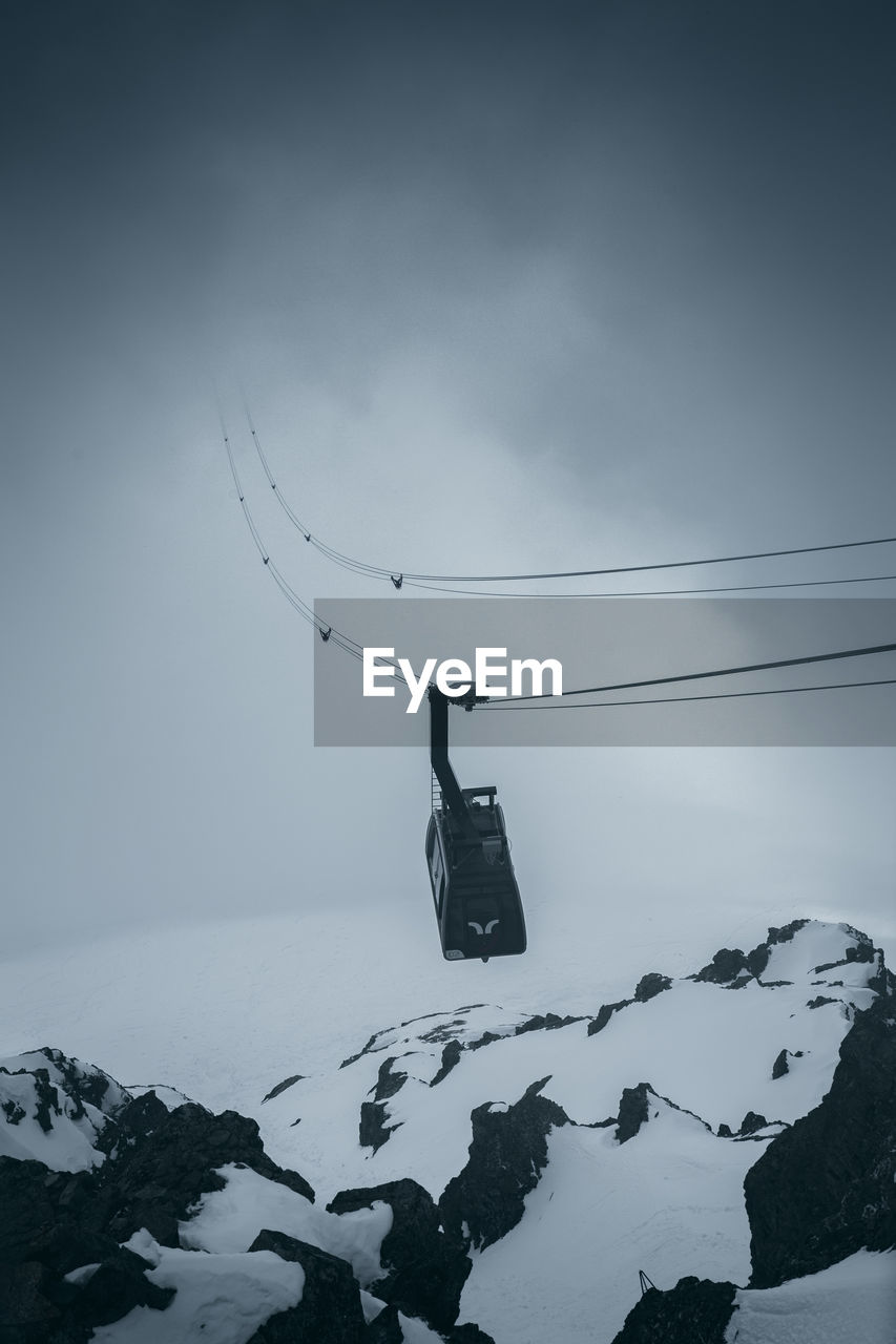 snow, winter, cold temperature, mountain, sky, scenics - nature, beauty in nature, covering, cable car, nature, tranquil scene, tranquility, overhead cable car, transportation, mode of transportation, day, environment, non-urban scene, travel, snowcapped mountain, no people, outdoors, extreme weather