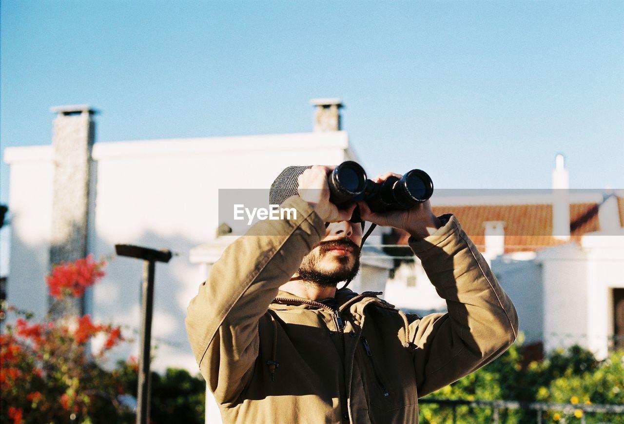 Man Using Binoculars While Standing Against Building