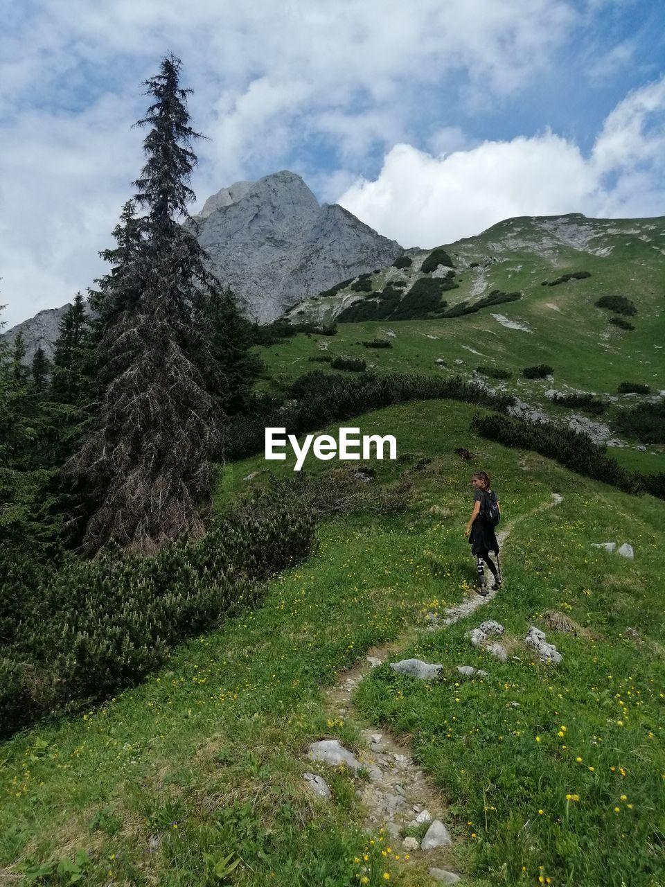Woman walking on mountain against sky