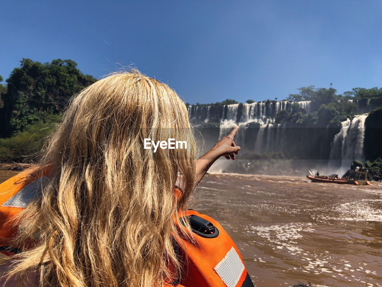 Rear view of woman pointing while rafting against waterfall and sky