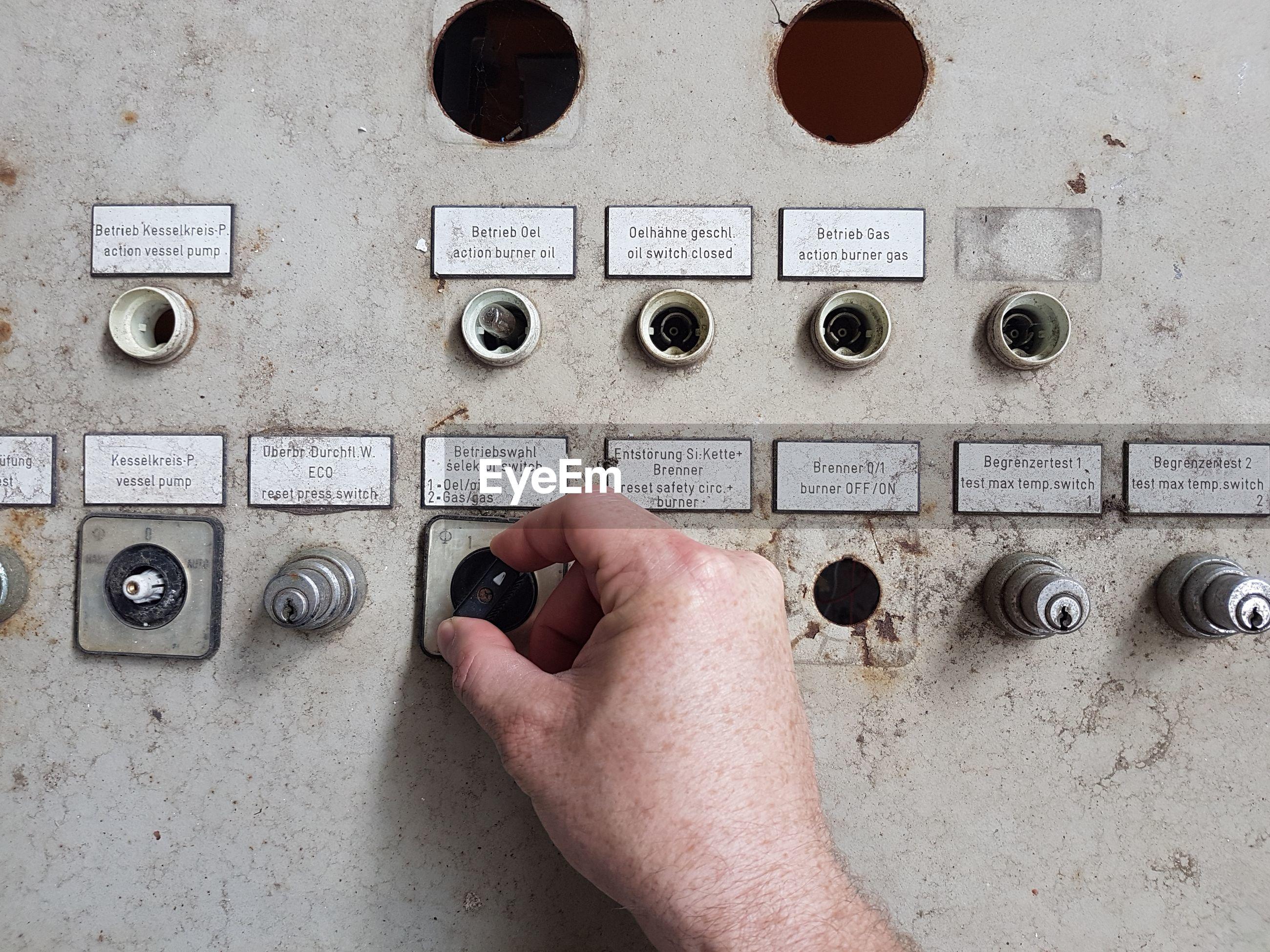 Cropped hand of man adjusting machinery knob