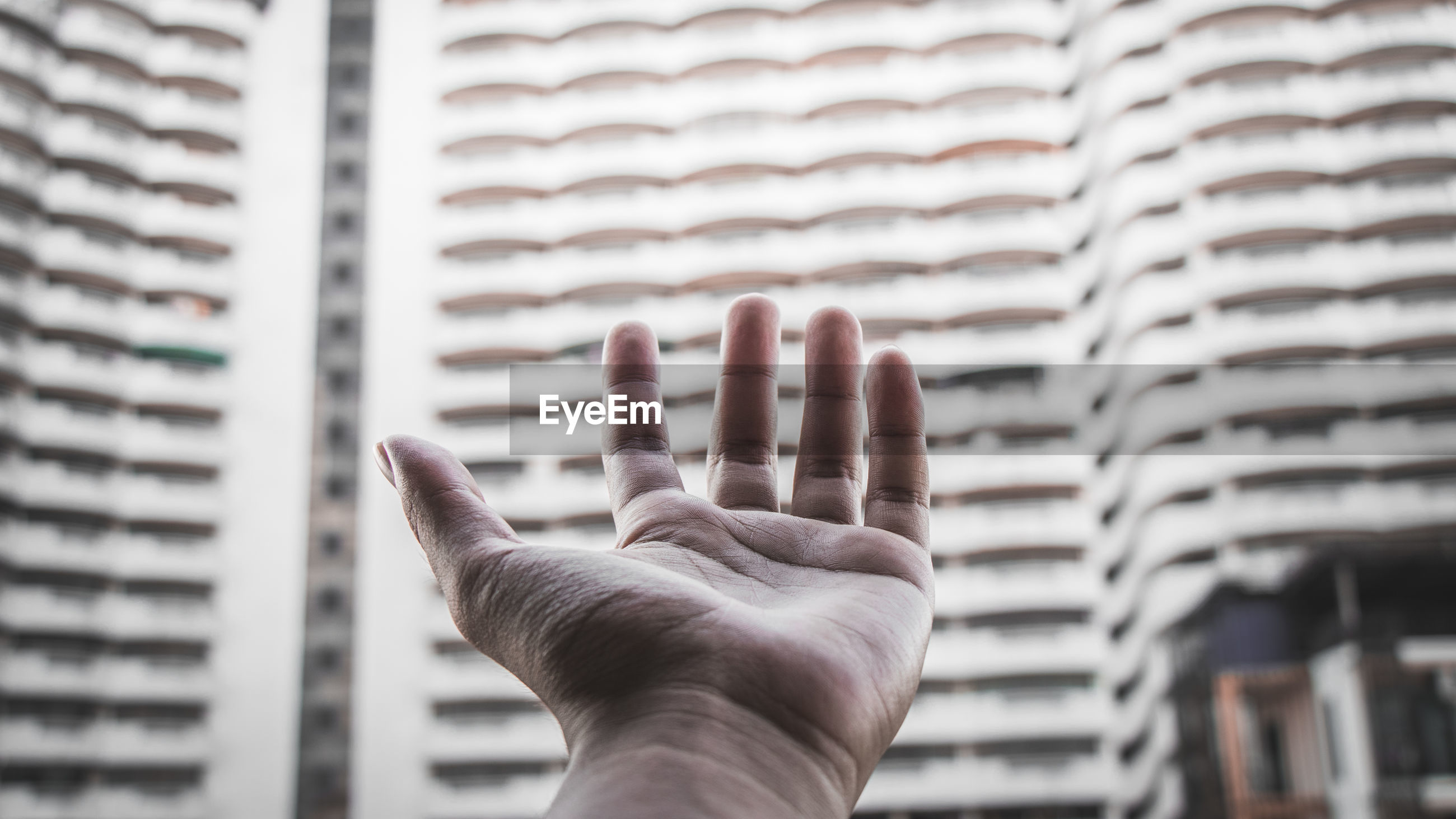 Cropped hand reaching buildings in city