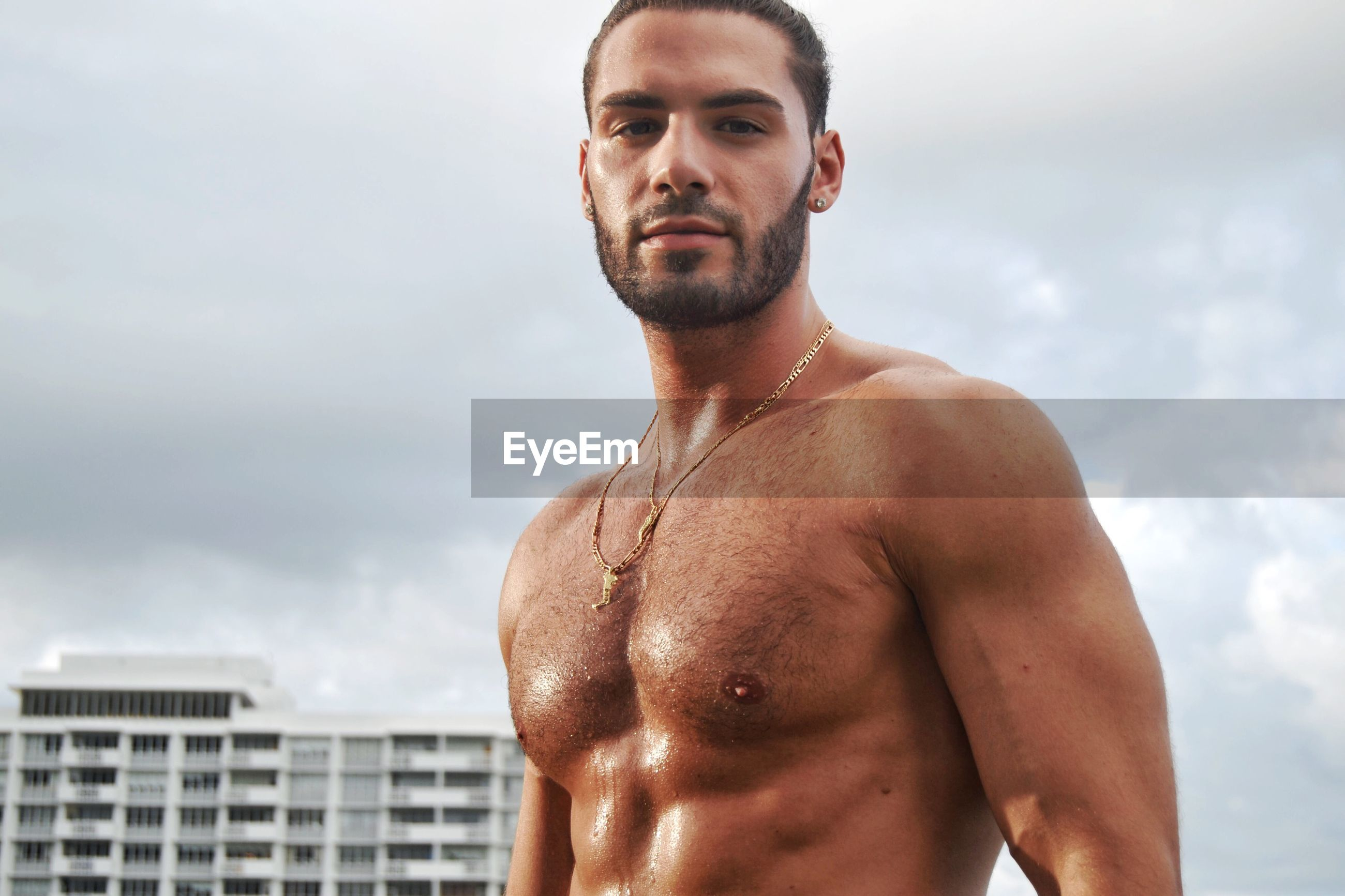 Portrait of shirtless muscular man standing against sky