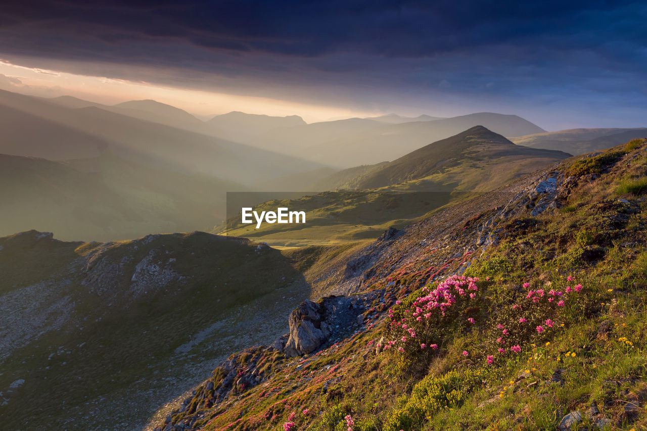 mountain, scenics - nature, beauty in nature, sky, non-urban scene, tranquil scene, mountain range, tranquility, environment, nature, landscape, idyllic, cloud - sky, remote, sunset, plant, day, real people, outdoors, leisure activity