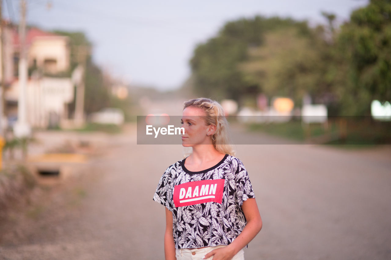 real people, focus on foreground, one person, front view, casual clothing, leisure activity, young adult, outdoors, standing, young women, blond hair, day, lifestyles
