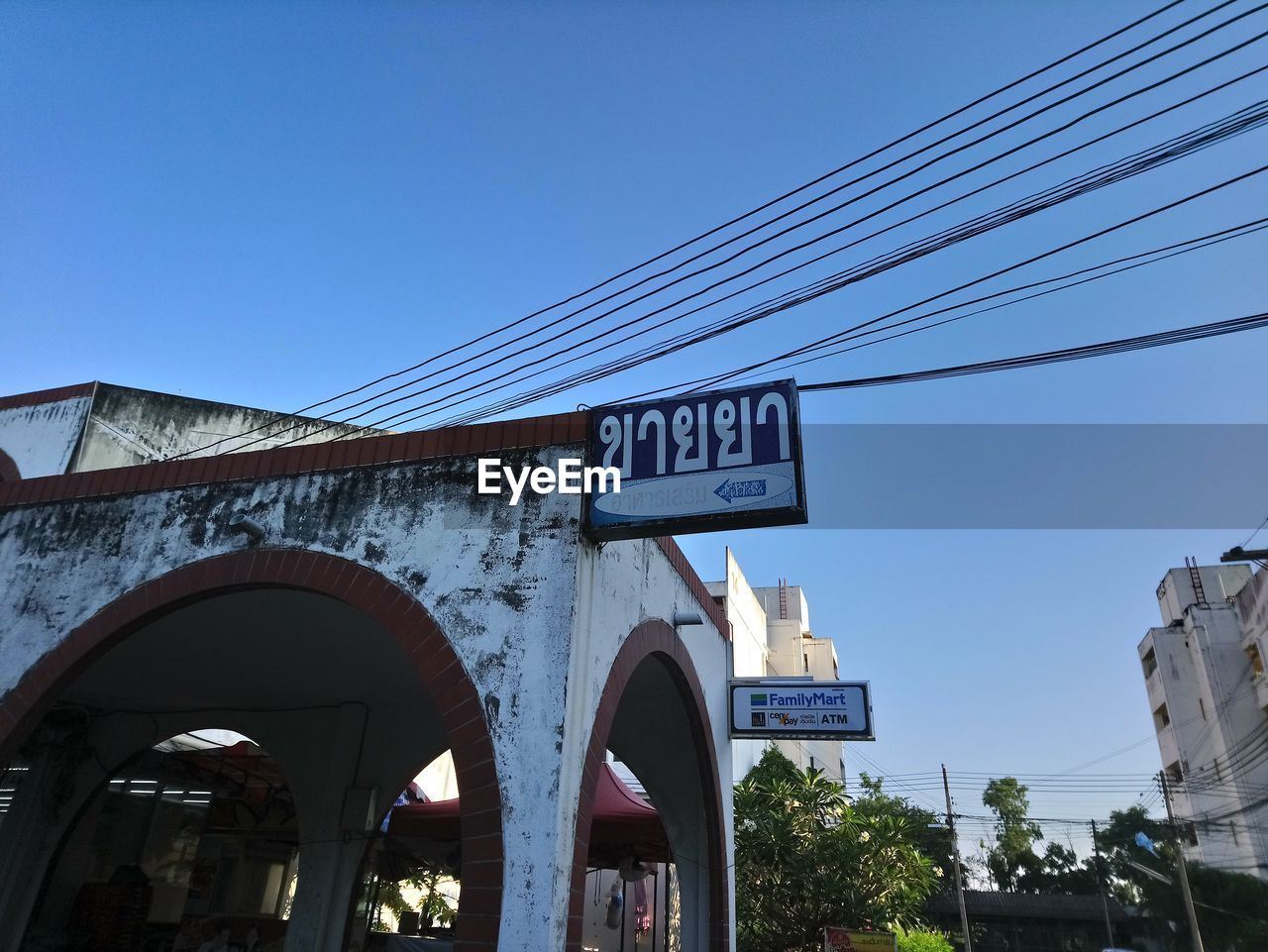 sky, architecture, low angle view, sign, built structure, communication, text, connection, nature, clear sky, building exterior, cable, blue, day, western script, information, no people, tree, information sign, city, outdoors, guidance, electricity