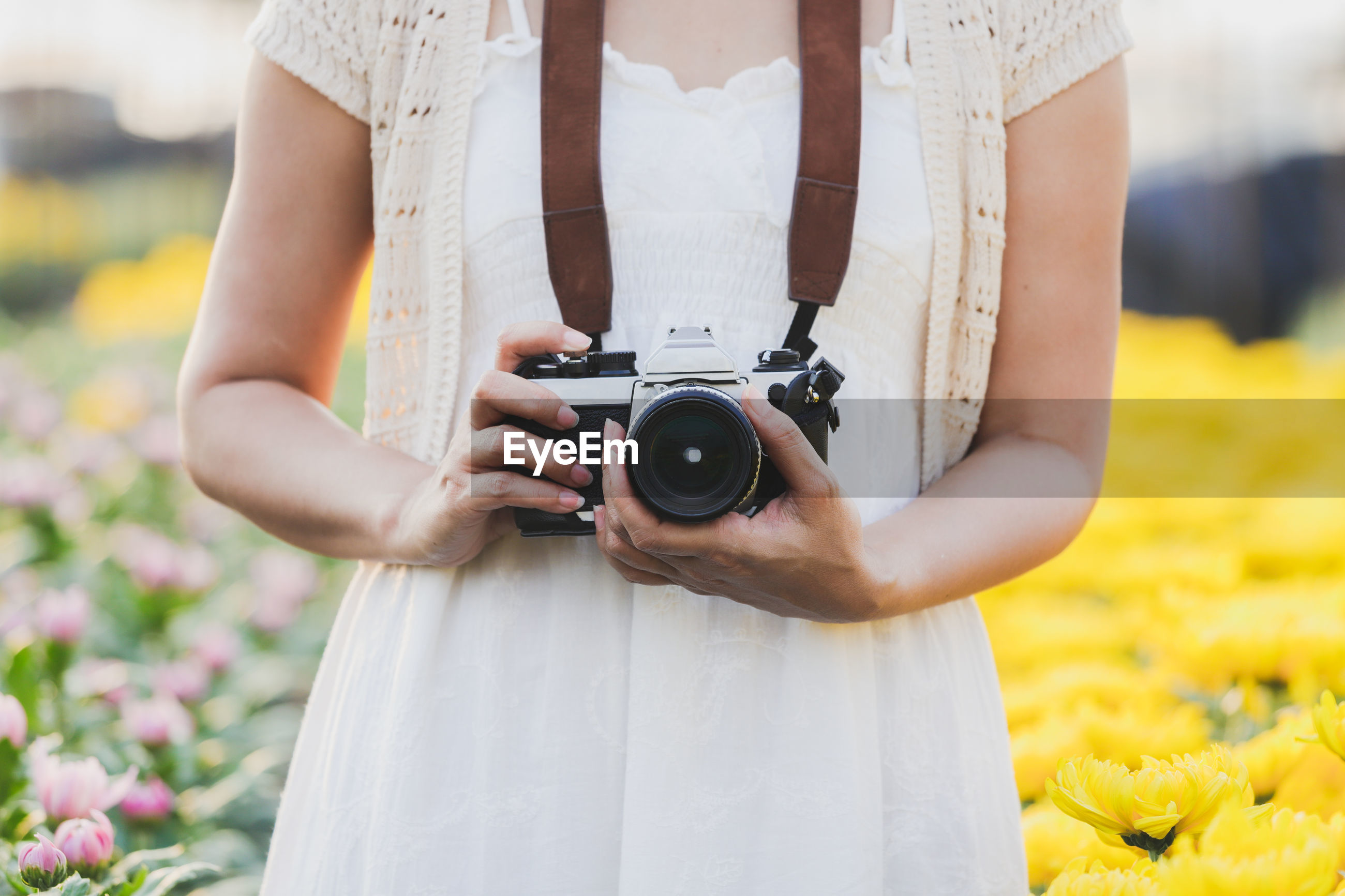 MIDSECTION OF WOMAN HOLDING CAMERA WHILE STANDING BY FLOWER