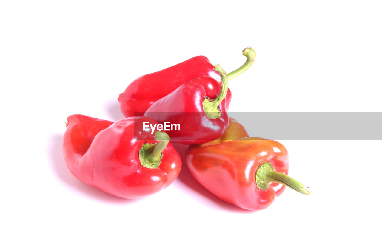 CLOSE-UP OF RED CHILI PEPPERS WITH WHITE BACKGROUND