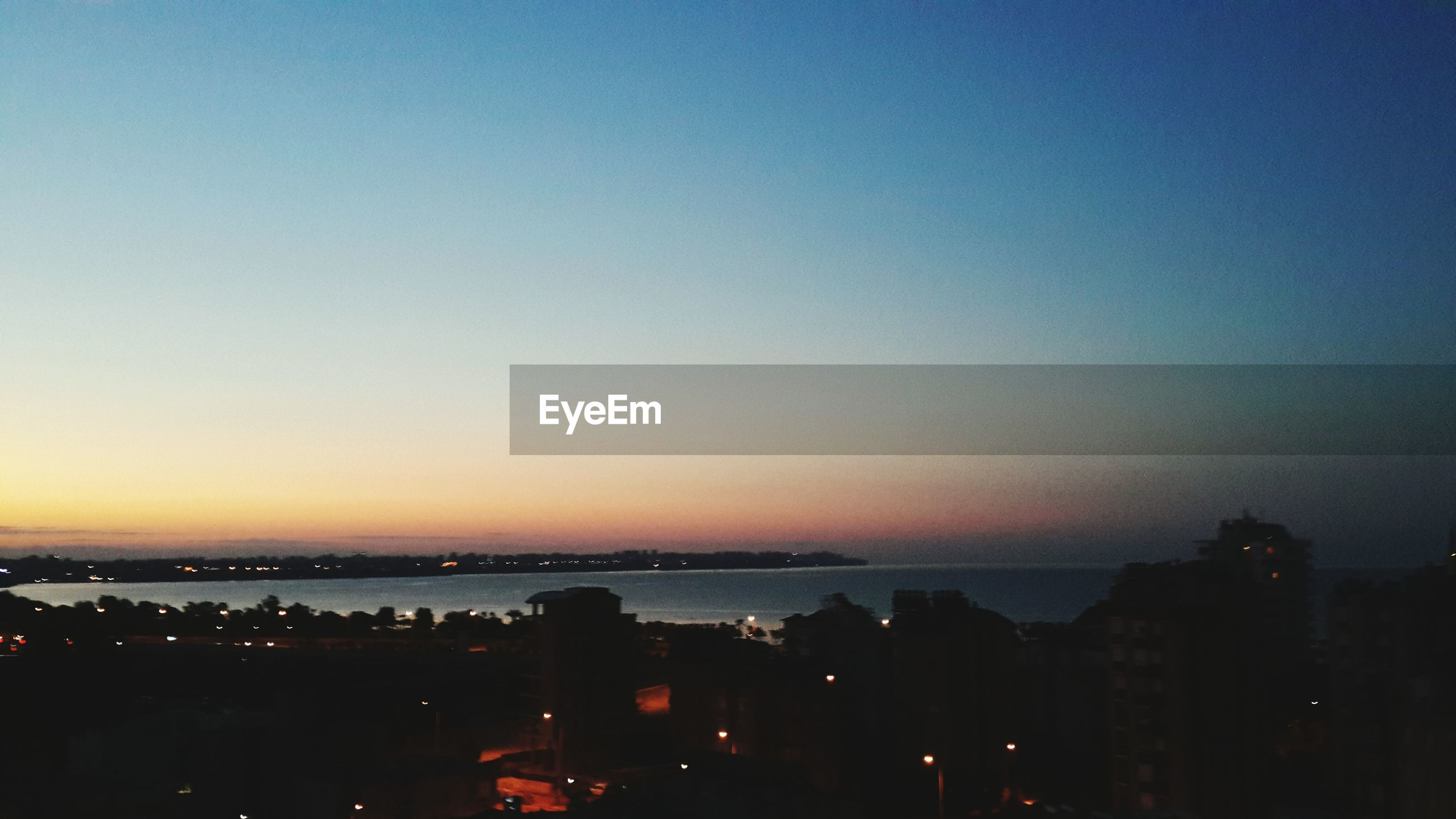 cityscape, city, building exterior, copy space, architecture, built structure, clear sky, sunset, illuminated, sea, water, crowded, high angle view, dusk, residential district, sky, scenics, residential building, residential structure, outdoors