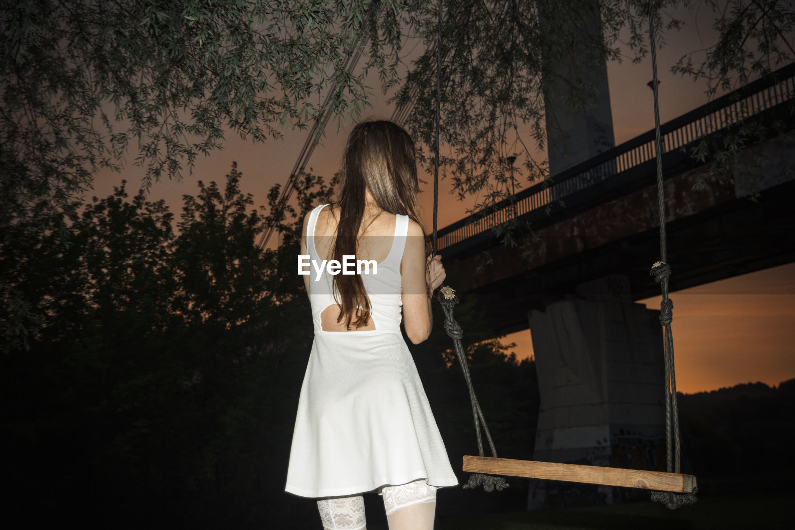 Rear view of woman standing by swing against trees