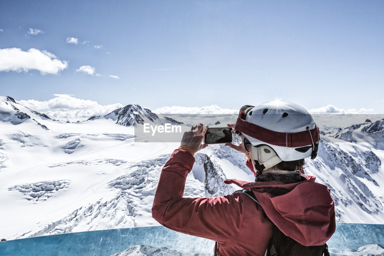 Rear View Of Man Photographing Through Mobile Phone Against Sky