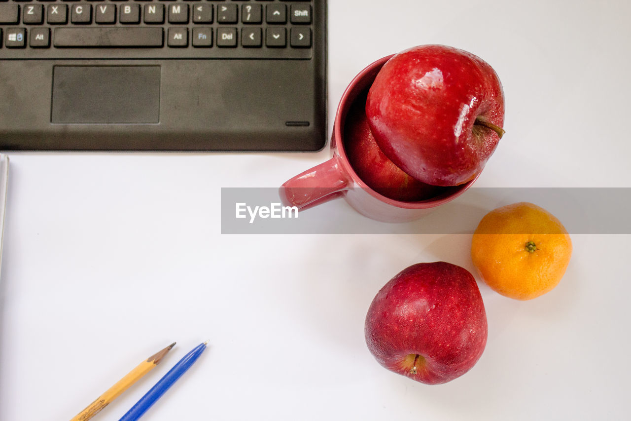 fruit, food and drink, indoors, technology, table, healthy eating, red, food, communication, freshness, close-up, white background, no people, computer keyboard, keyboard, day