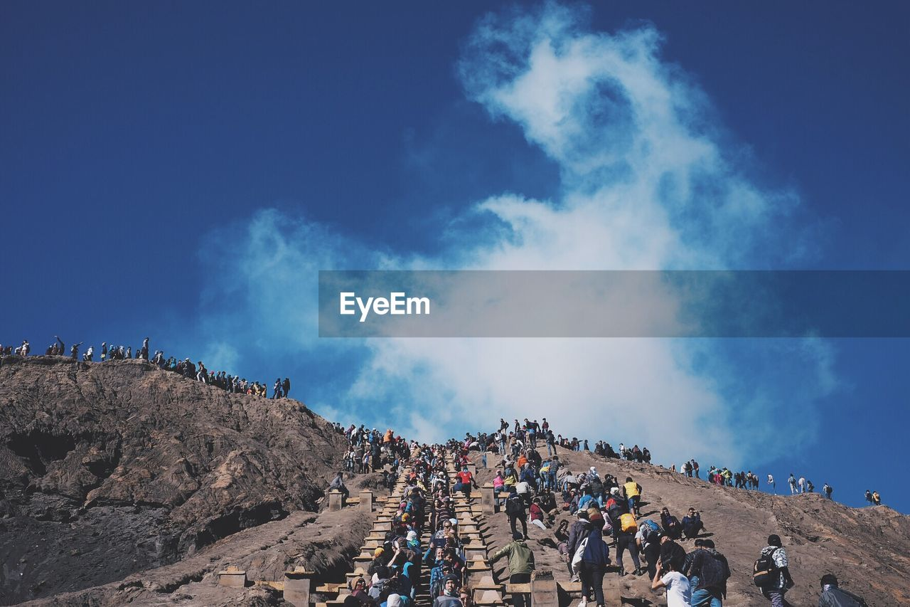 People Climbing On Mountains Against Blue Sky