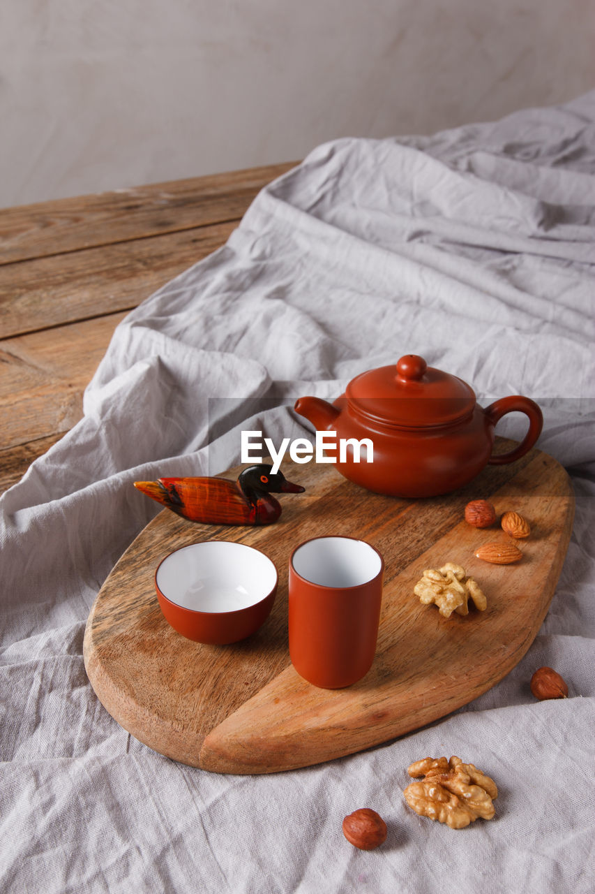 HIGH ANGLE VIEW OF ORANGE AND TEA ON BED