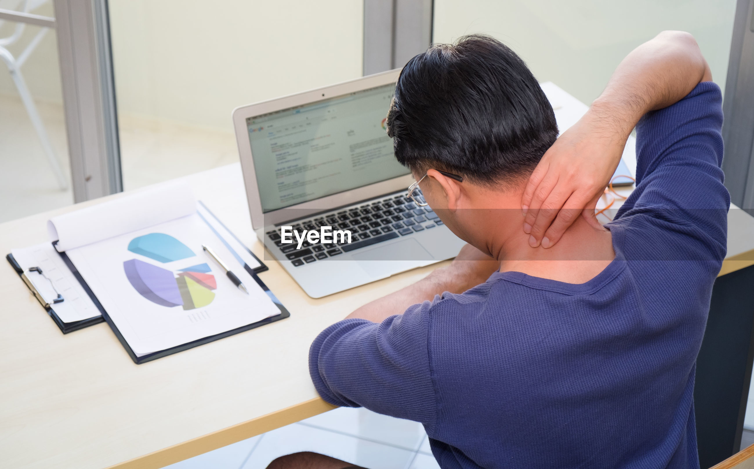 Rear view of man with neckache using laptop at table