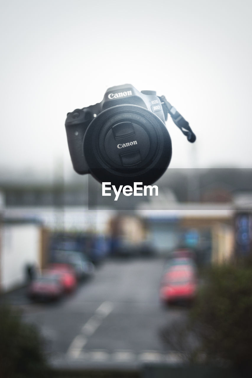 camera - photographic equipment, focus on foreground, no people, technology, transportation, day, outdoors, photography themes, modern, close-up, architecture, digital single-lens reflex camera, sky
