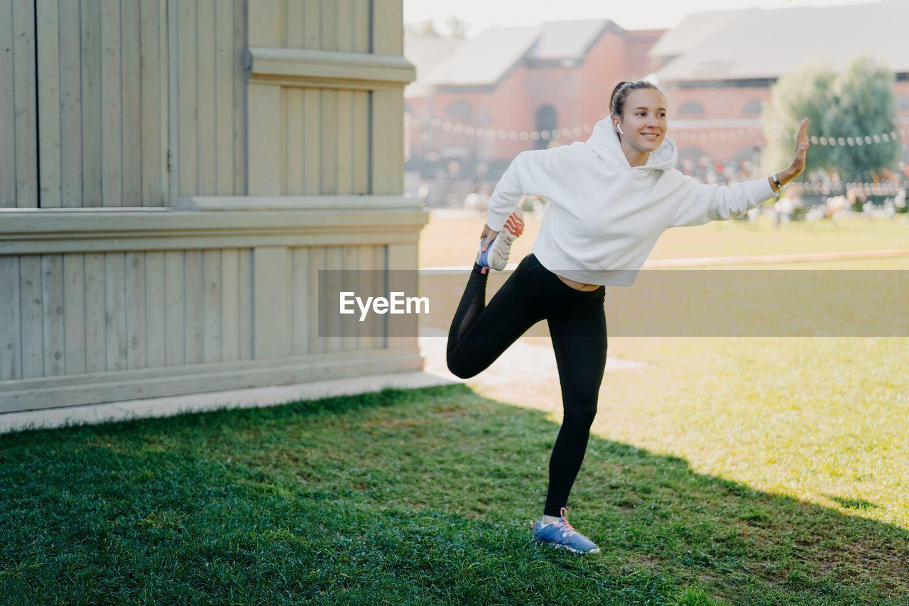 Full length of girl exercising outdoors