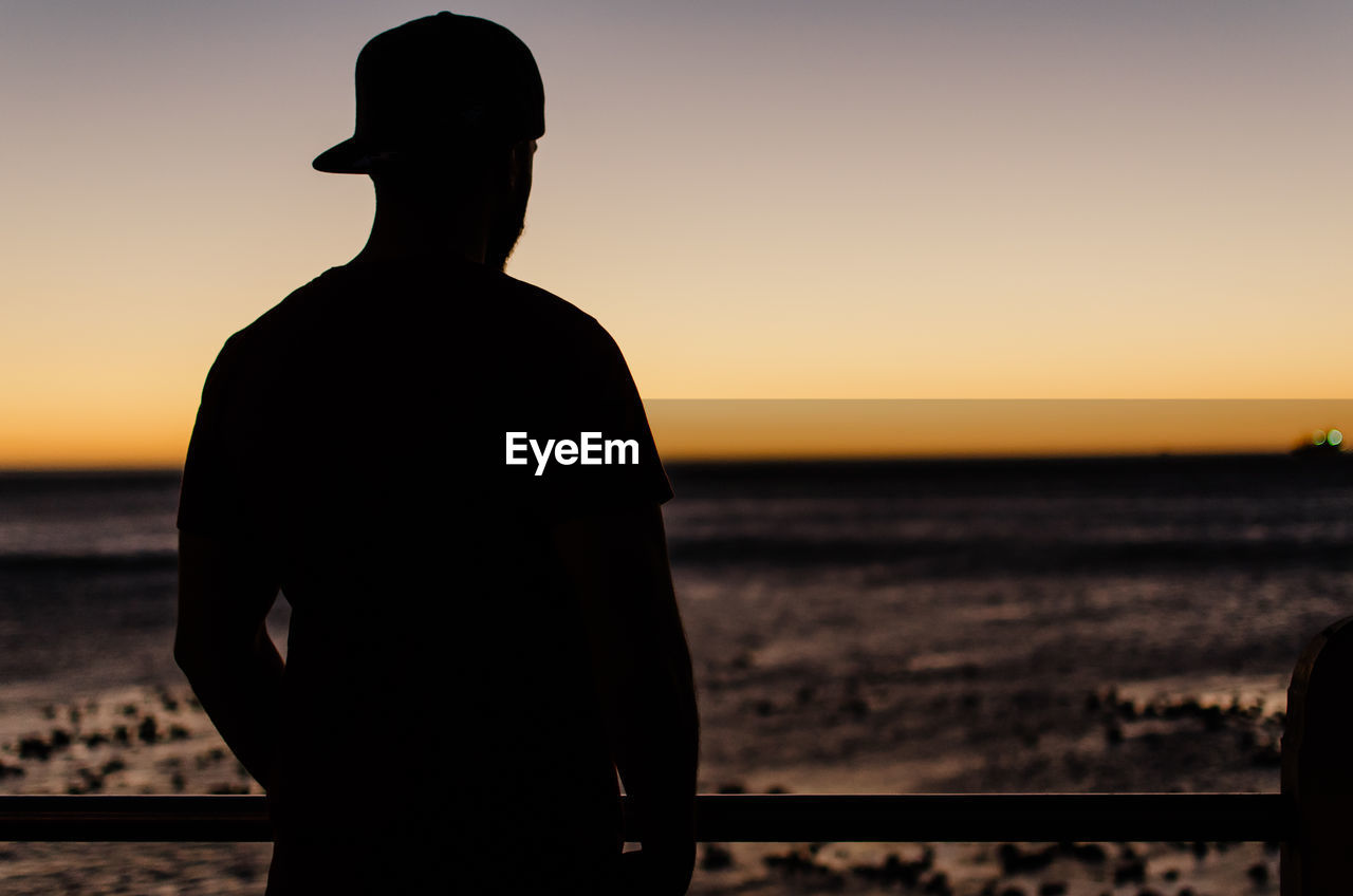 Silhouette man looking at landscape against sky during sunset