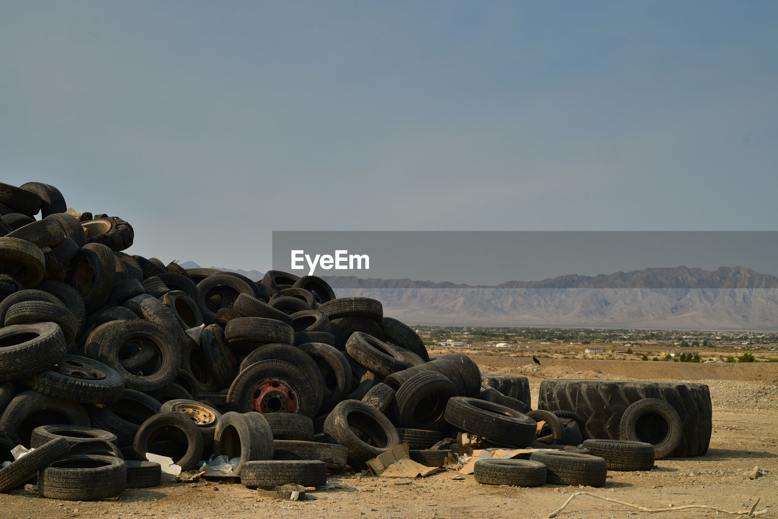 Worn-out vehicle tires piled in mojave desert with distant mountains in town of pahrump, nevada, usa