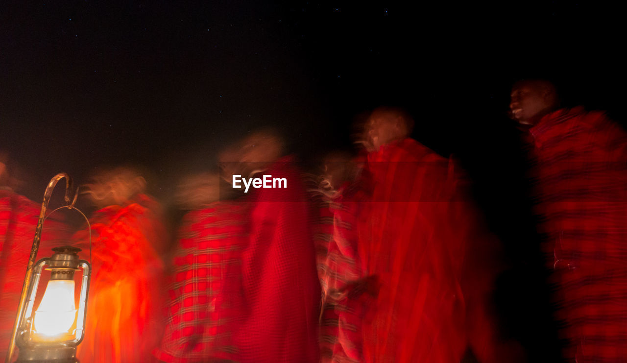 BLURRED MOTION OF PEOPLE AT ILLUMINATED RED NIGHT