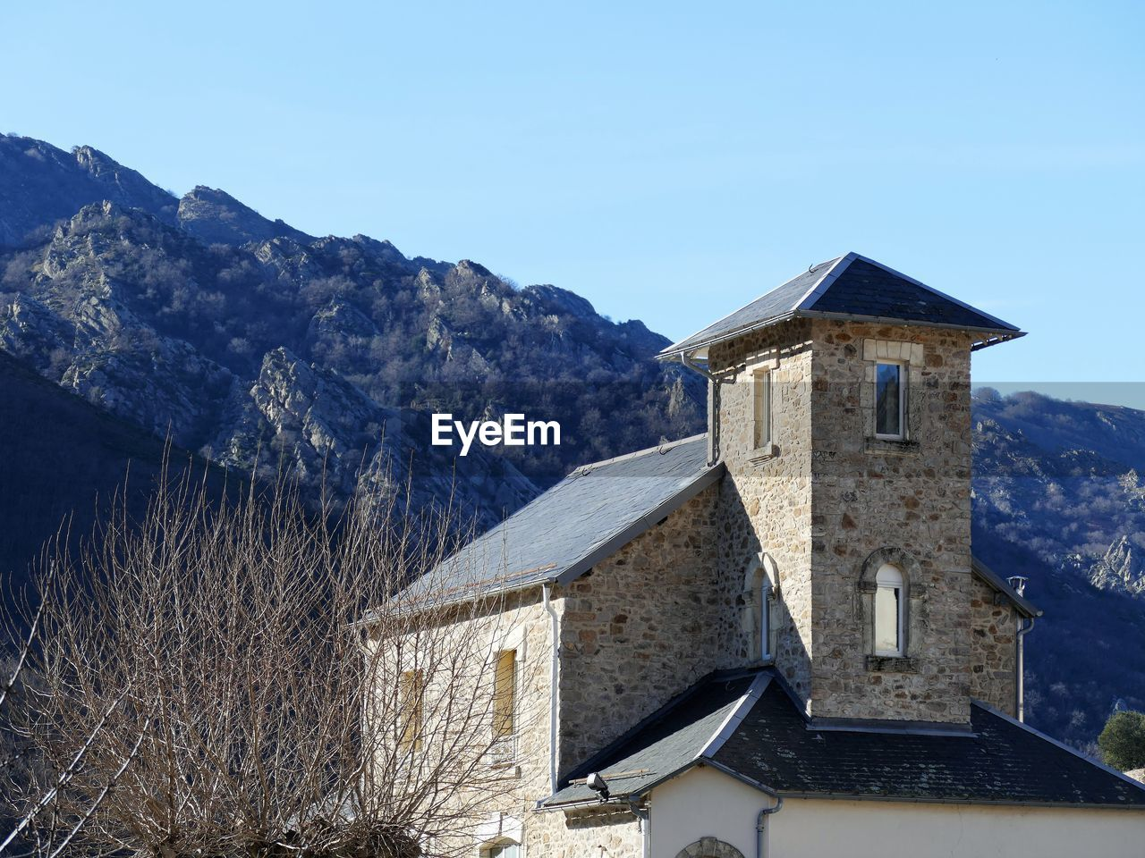 architecture, built structure, building exterior, building, mountain, sky, nature, house, no people, day, clear sky, mountain range, residential district, outdoors, tree, cold temperature, religion, place of worship, blue, low angle view