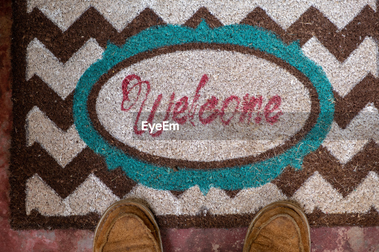 shoe, low section, text, one person, western script, standing, close-up, multi colored, directly above, human body part, body part, communication, high angle view, personal perspective, day, indoors, creativity, flooring, human foot, ornate