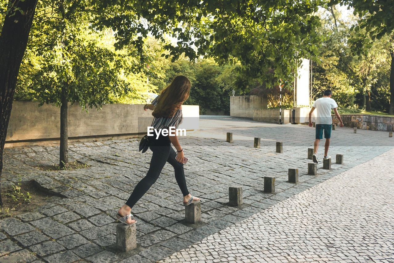full length, tree, plant, real people, casual clothing, walking, footpath, rear view, leisure activity, lifestyles, women, people, adult, day, nature, two people, outdoors, architecture, long hair, hairstyle, paving stone