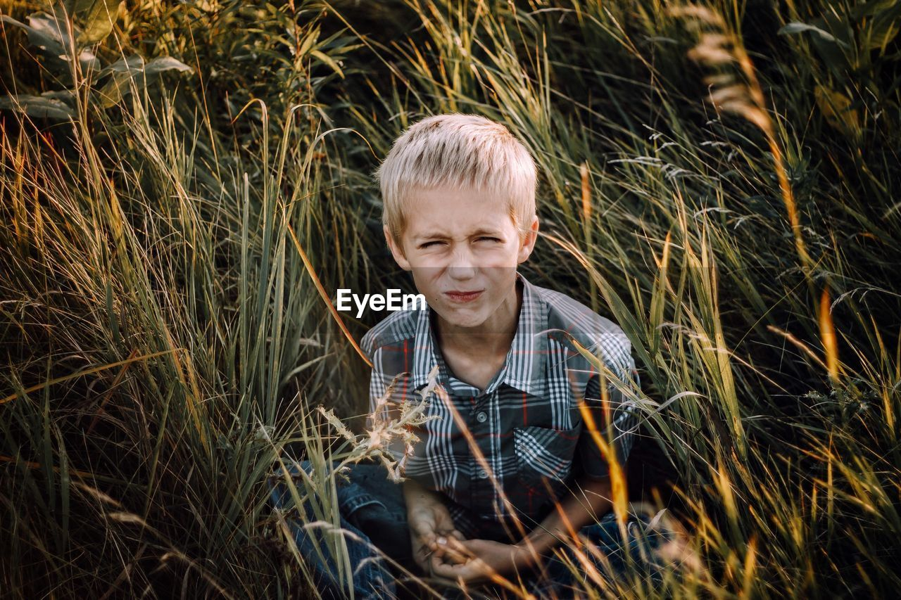 plant, child, blond hair, one person, childhood, front view, grass, leisure activity, portrait, men, nature, males, casual clothing, headshot, lifestyles, growth, boys, real people, hair, outdoors