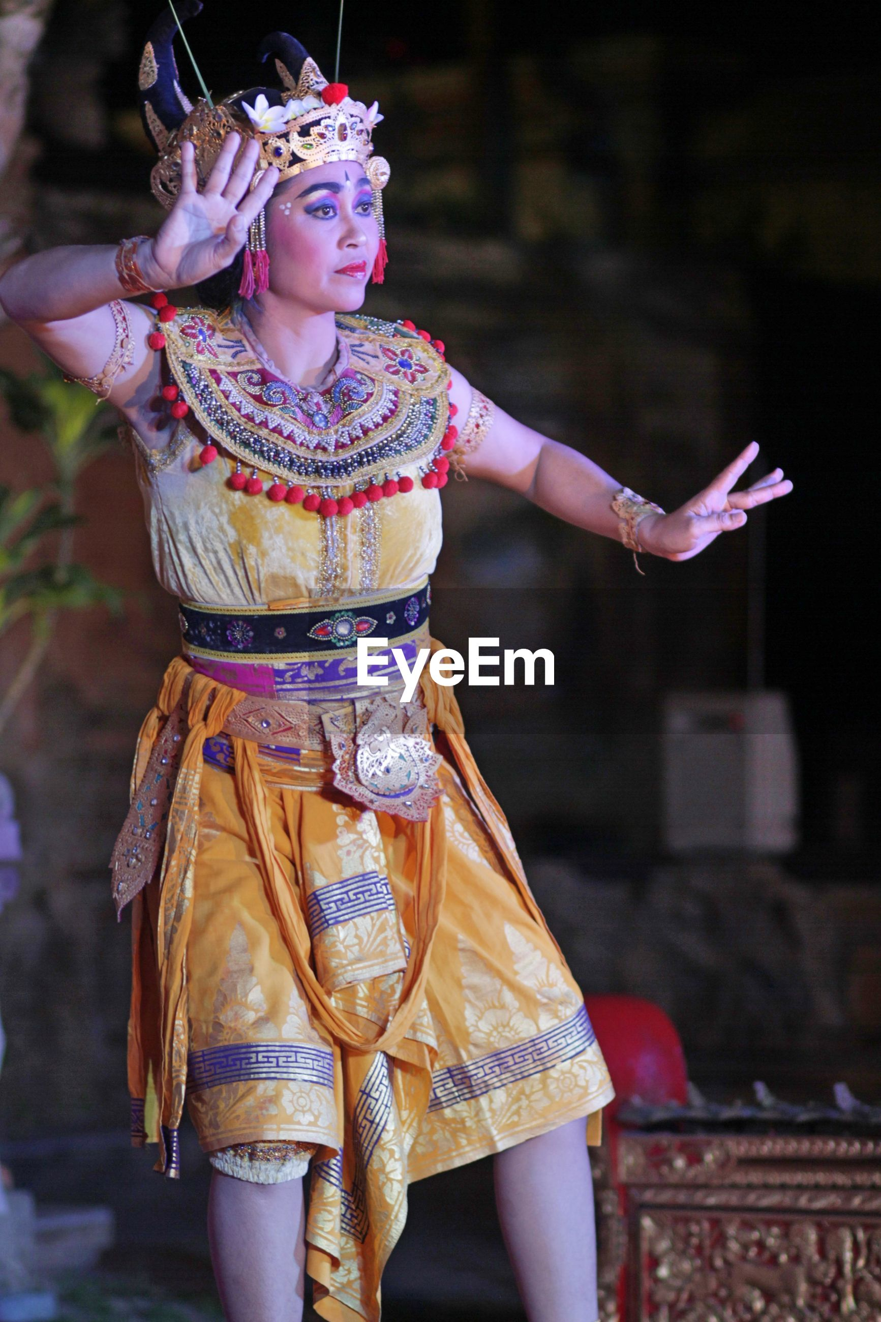 MIDSECTION OF WOMAN DANCING IN TRADITIONAL CLOTHING OUTDOORS