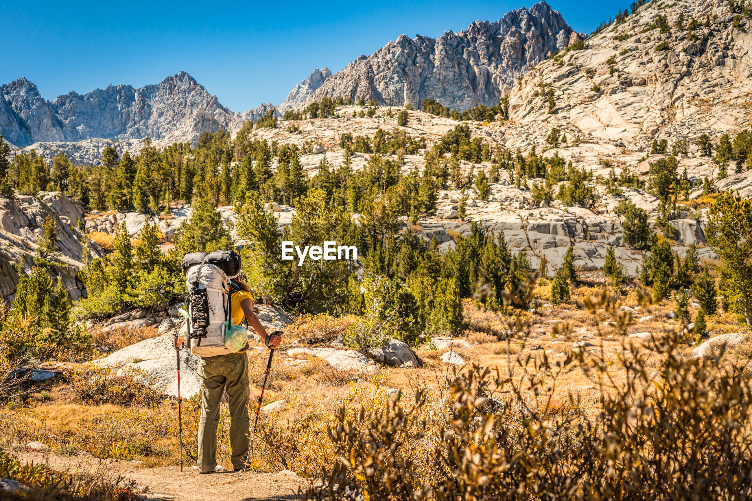 Rear view of hiker holding hiking poles while standing on cliff in front of mountain ranges against sky
