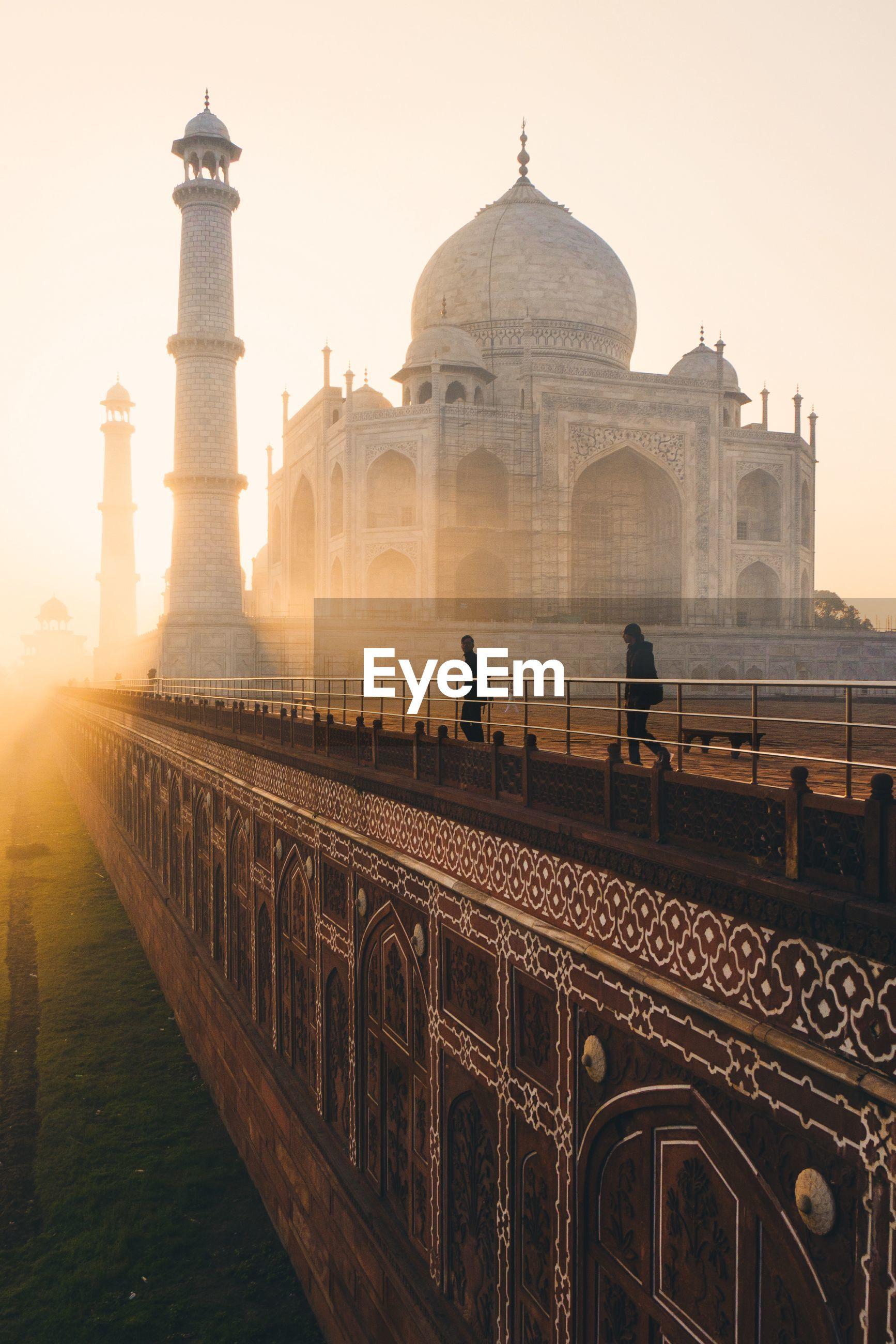 Tourist visiting taj mahal during sunrise