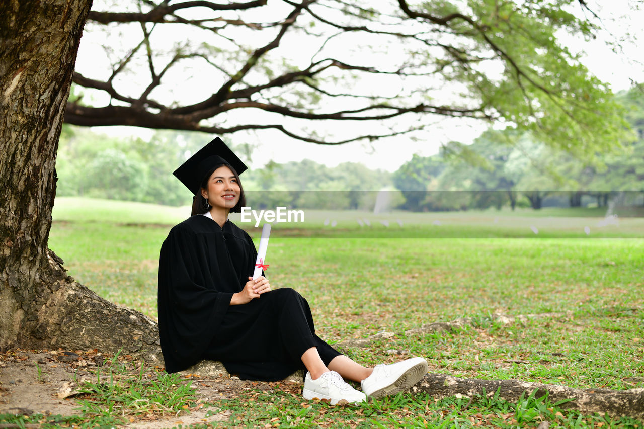 plant, one person, real people, tree, grass, sitting, lifestyles, day, nature, focus on foreground, education, field, full length, land, young adult, graduation, leisure activity, mortarboard, outdoors