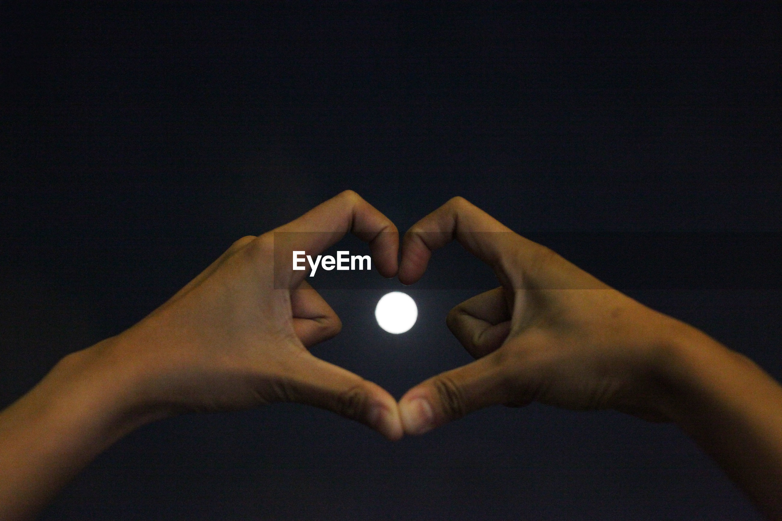 Cropped hands making heart shape against full moon at night
