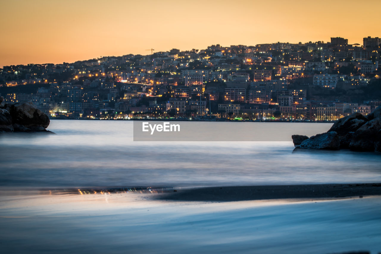 water, sky, building exterior, sea, architecture, built structure, sunset, city, nature, waterfront, cityscape, no people, beauty in nature, land, beach, building, rock, outdoors, scenics - nature