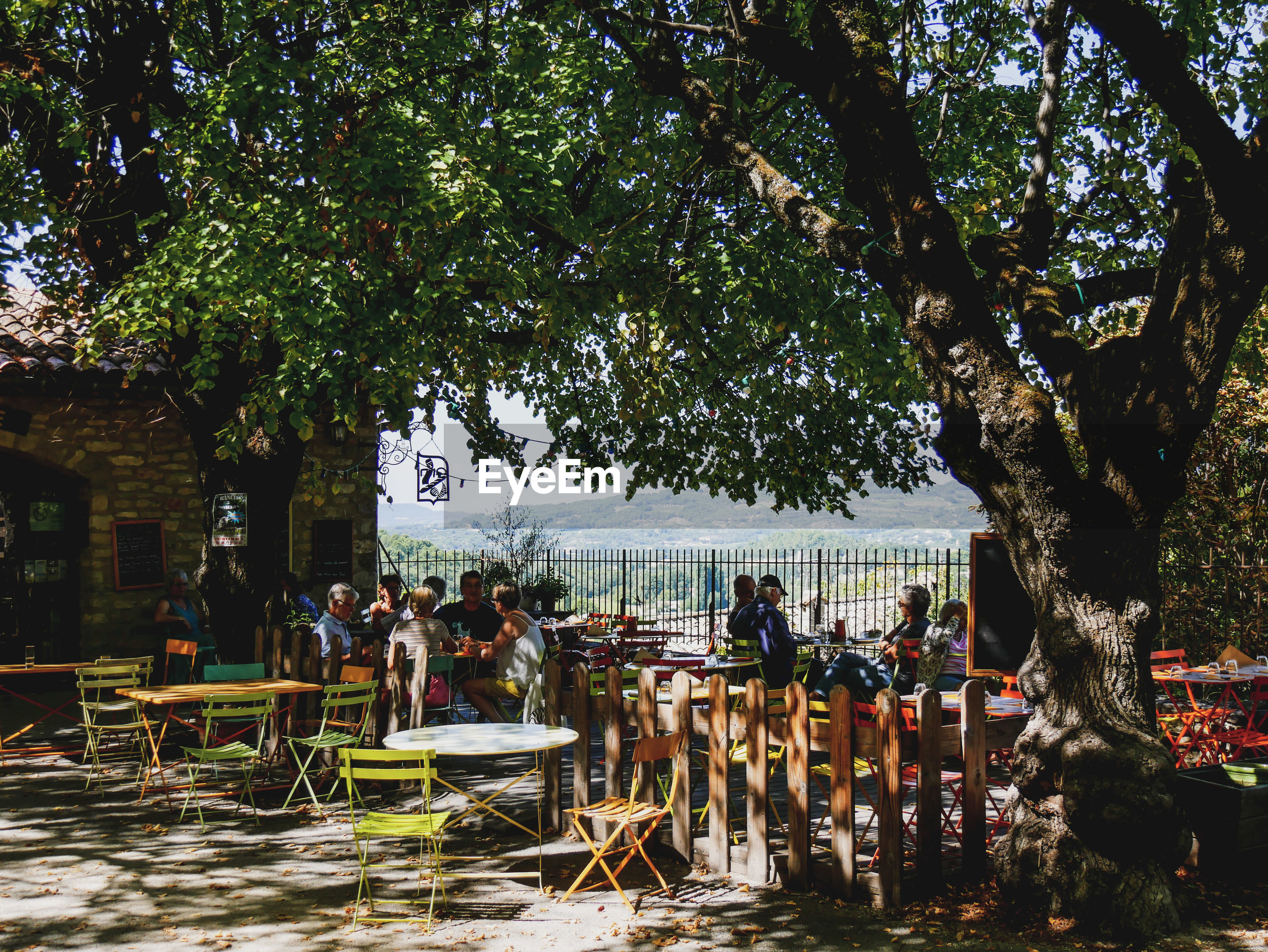 People sitting at sidewalk cafe by trees