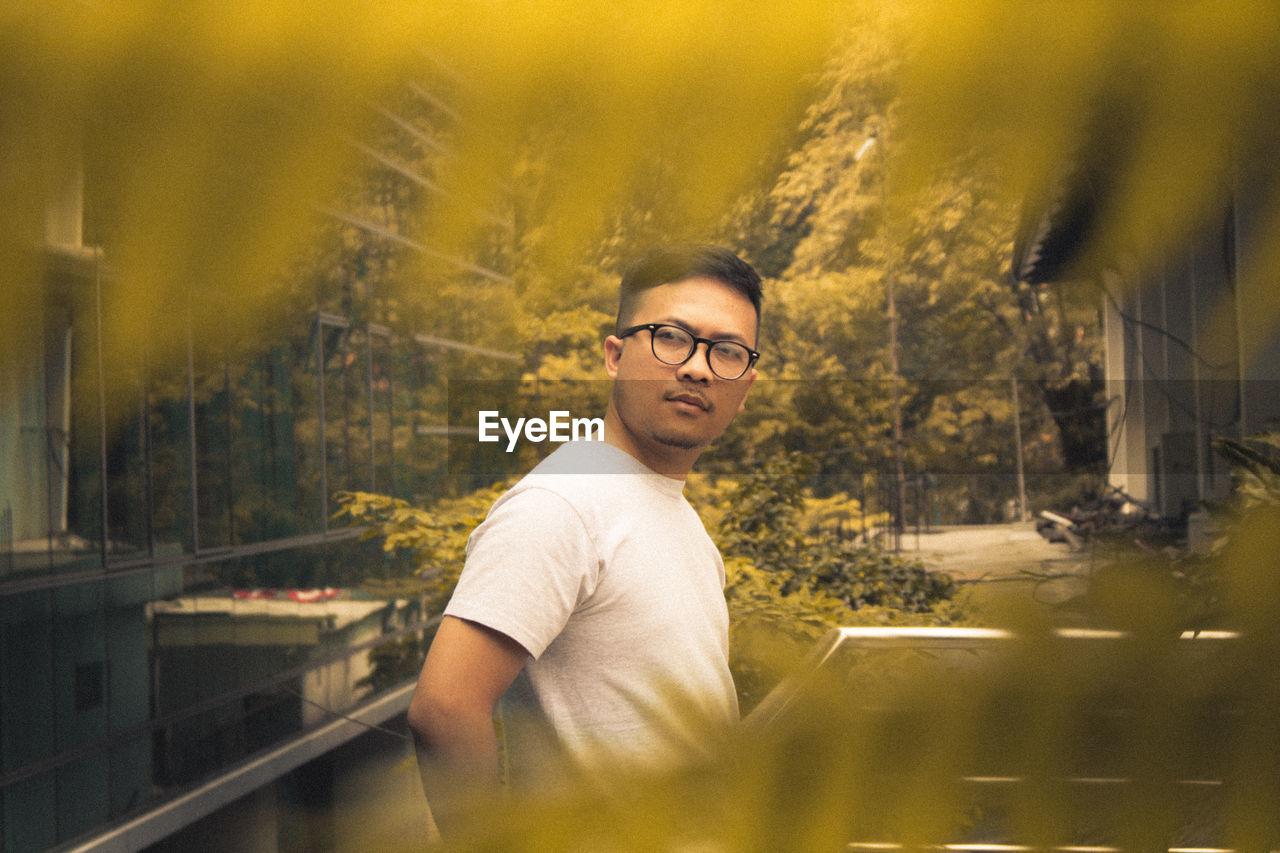 Thoughtful Man Wearing Eyeglasses Seen Through Leaves