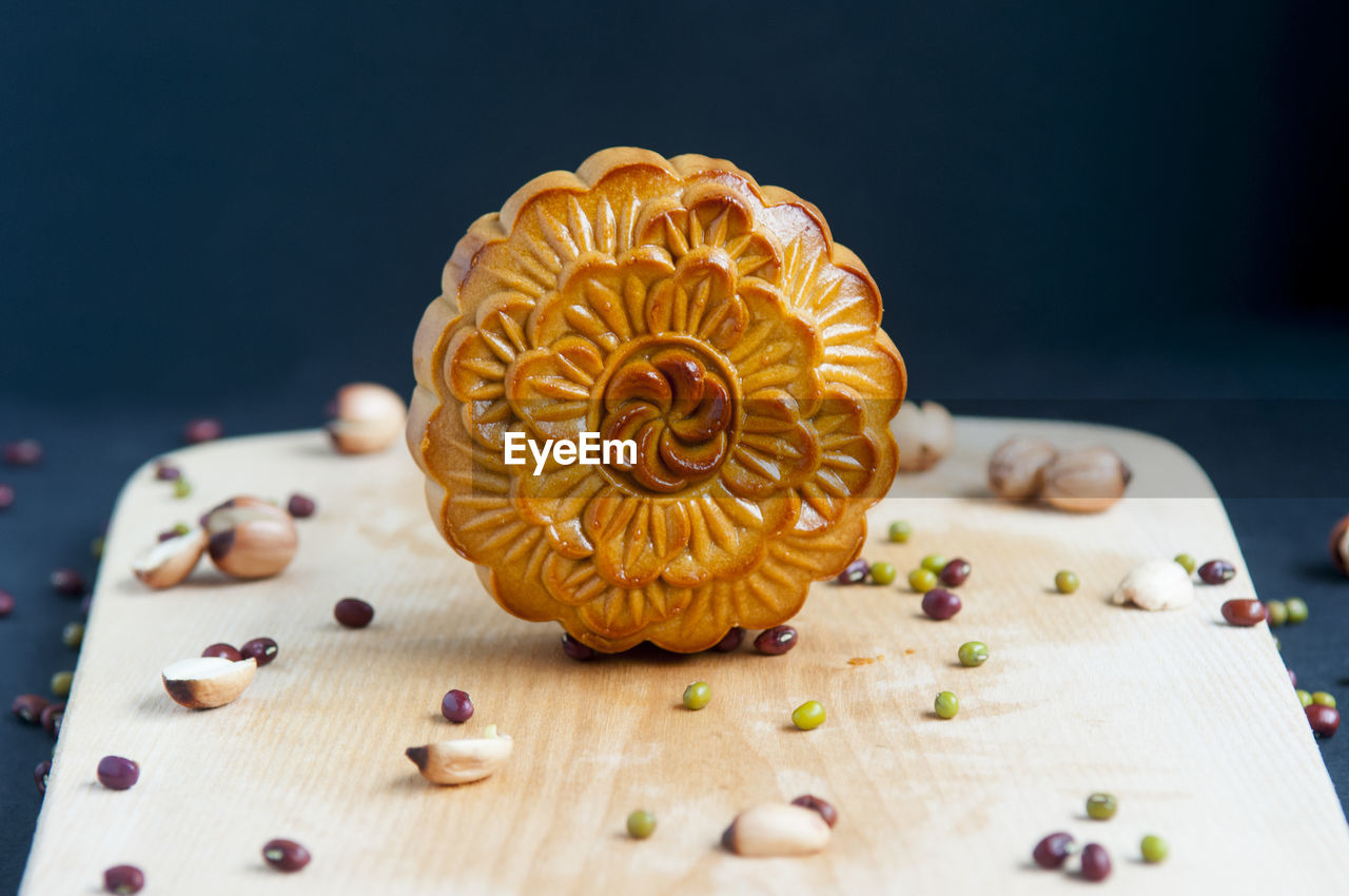 Close-up of moon cake with seeds on serving board against black background