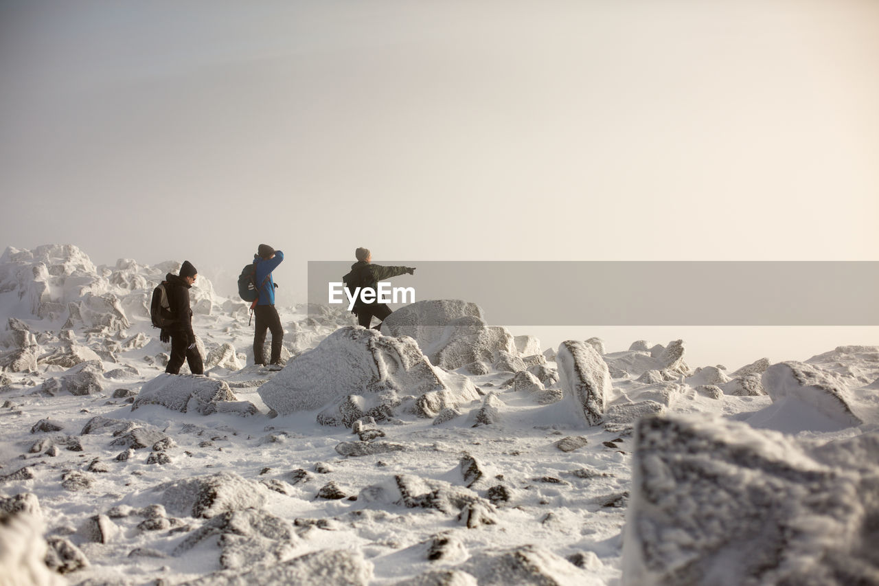 real people, nature, full length, outdoors, rock - object, leisure activity, clear sky, sky, sunlight, beauty in nature, lifestyles, winter, togetherness, sand, day, scenics, adventure, cold temperature, vacations, snow, men, mountain, arid climate, salt - mineral, people