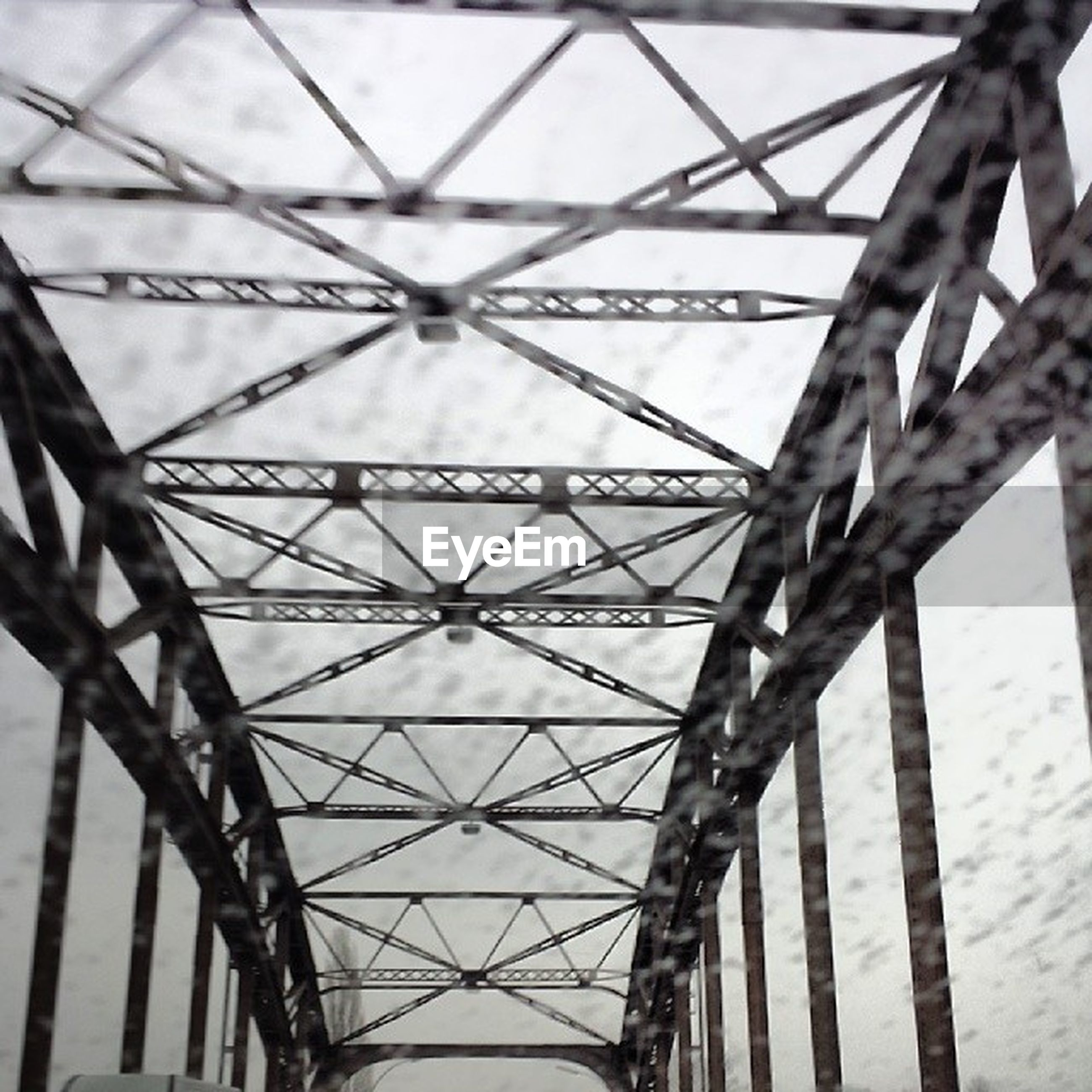 low angle view, metal, connection, built structure, metallic, architecture, engineering, pattern, sky, grid, day, no people, directly below, electricity pylon, outdoors, bridge - man made structure, design, diminishing perspective, close-up