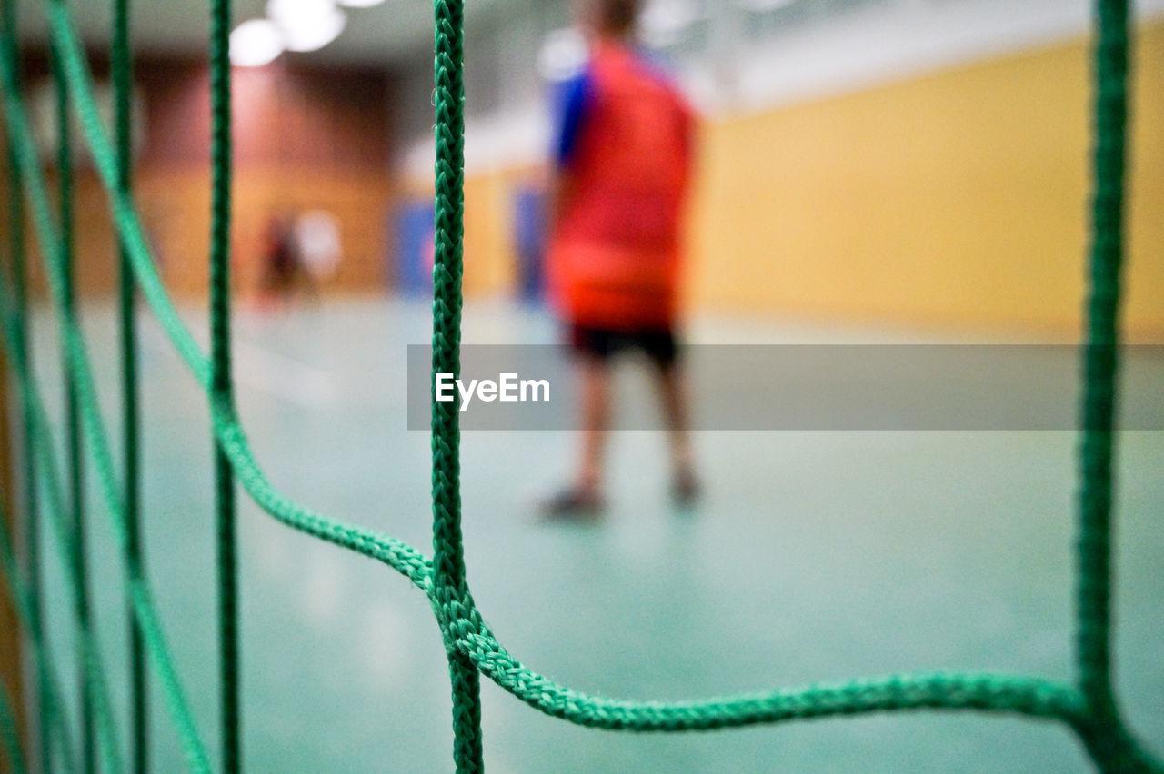 Rear view of sportsperson seen through net