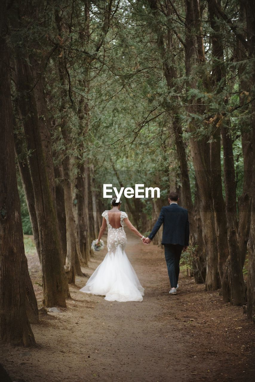 Rear View Of Couple Walking In Forest