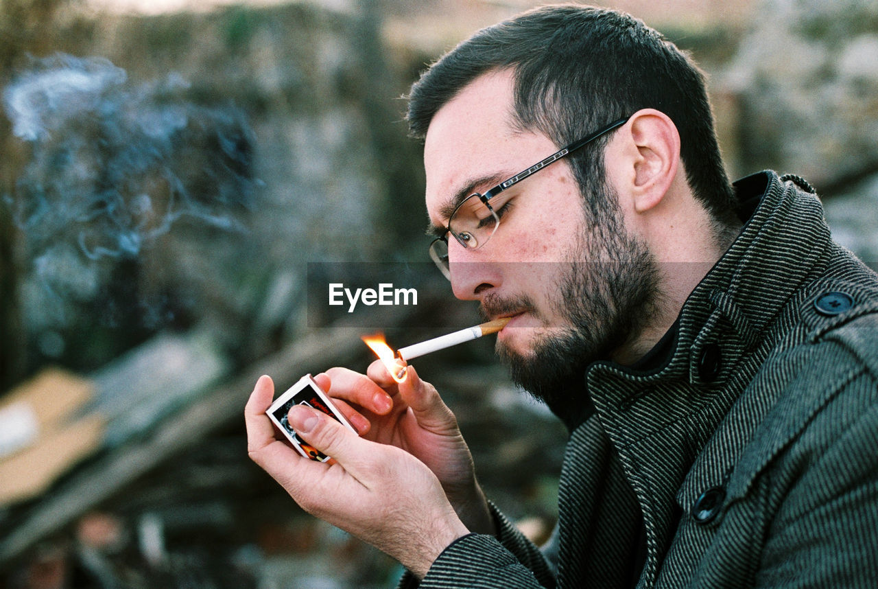 Close-Up Of Man Igniting Cigarette