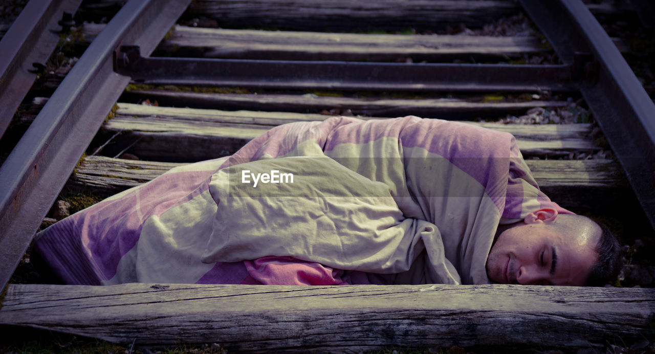 Young man sleeping on railroad tracks