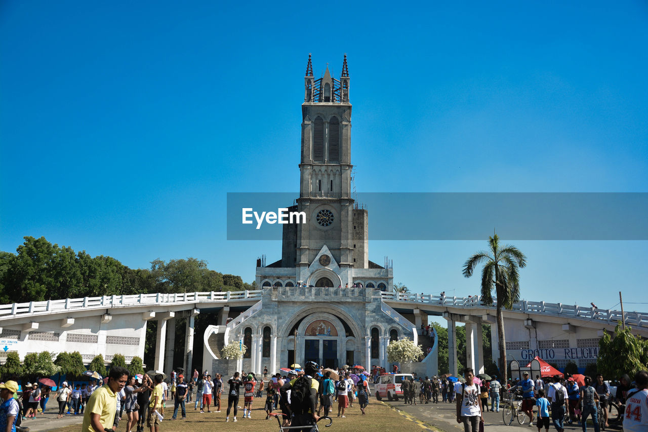 architecture, built structure, sky, building exterior, group of people, crowd, blue, large group of people, place of worship, nature, real people, religion, travel, tourism, day, clear sky, belief, travel destinations, outdoors